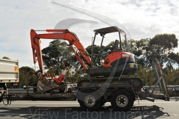 Excavator on trailer in motion