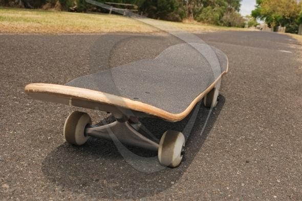 Skateboard on asphalt footpath