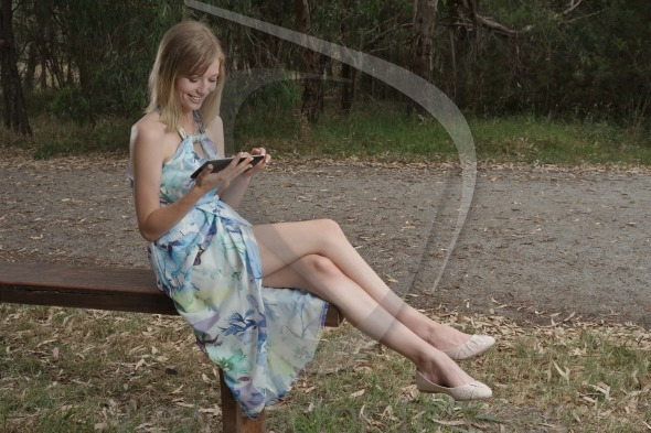 Woman with tablet on bench